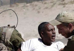 African migrant being dragged by Israeli soldiers.